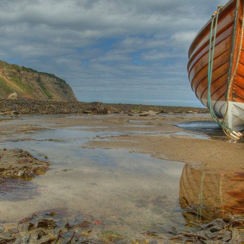 fishing boat on shore with buoy